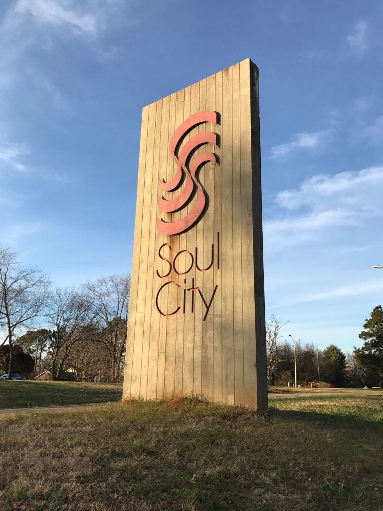 """The marquee for Soul City: a large rectangular upright sign with distinctive red """"swooshes""""."""